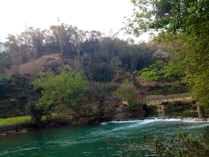 河道蜿蜒曲折,水车散落其间,布依村寨沿河而布,更显生动.