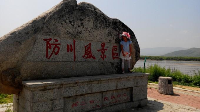 """大堤北侧起始段立有""""防川风景名胜区""""和""""联合国世界公园""""两块石碑."""